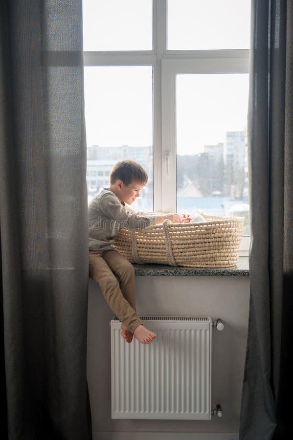 Weinig broer zit dichtbij het venster met himnewbornzuster in de wieg Kinderen met klein leeftijdsverschil royalty-vrije stock fotografie