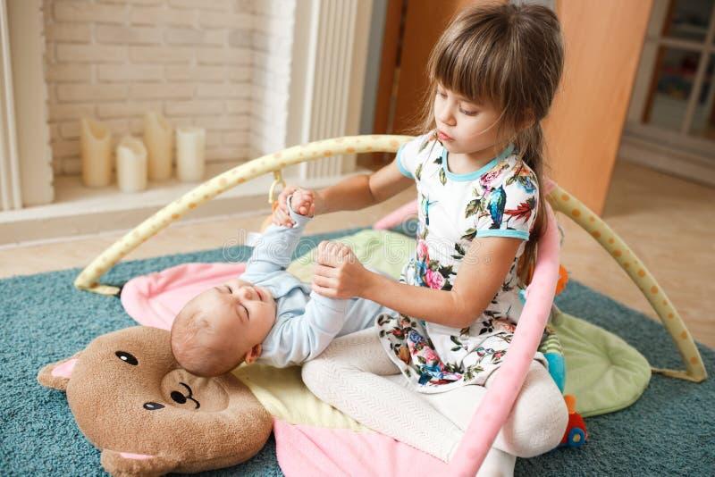 Weinig charmant meisje houdt handen haar uiterst kleine broer liggend op het tapijt op de vloer in de ruimte royalty-vrije stock afbeeldingen