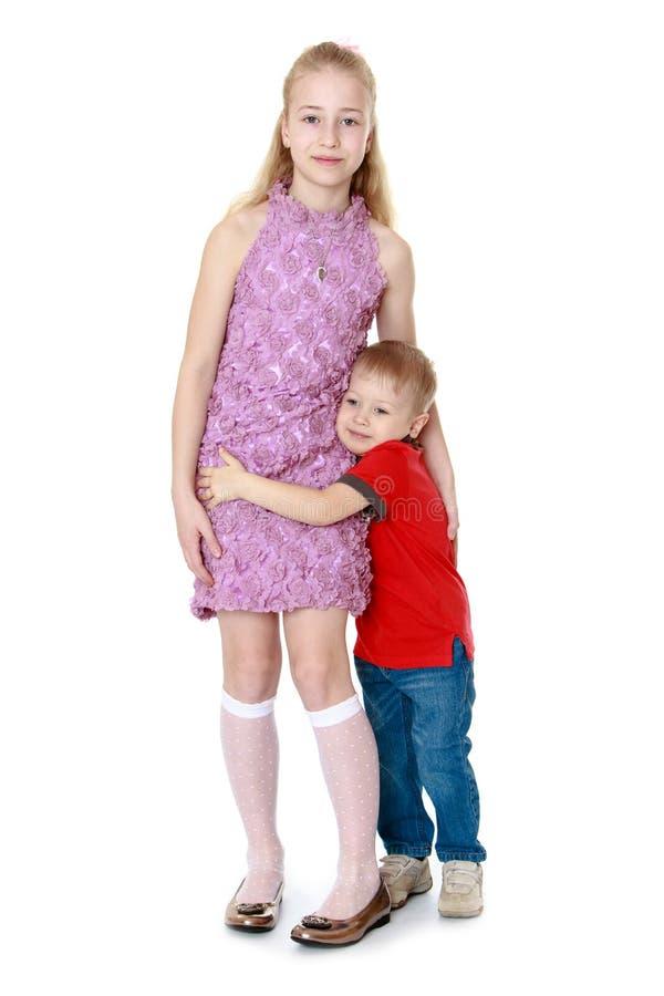 Weinig charmante jongen klampte zich aan zijn oudere zuster vast, hij stock afbeeldingen