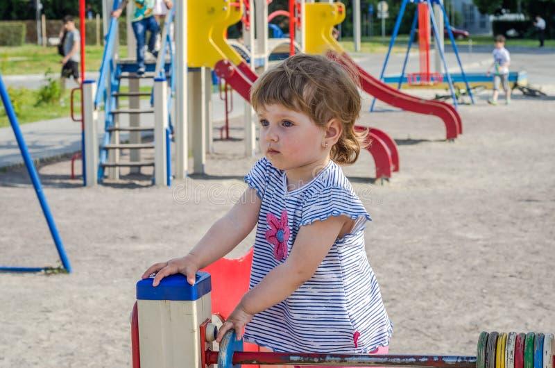 Weinig charmante meisjesbaby die op de speelplaats spelen die op een schommeling berijden, die de gekleurde vormen tellen stock foto's