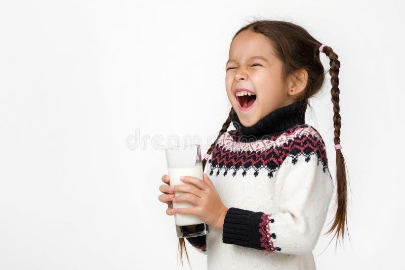 Weinig de holdingsglas van het kindmeisje melk op witte achtergrond royalty-vrije stock fotografie