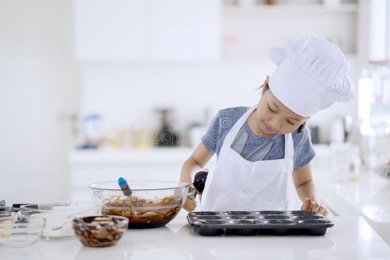 Weinig deeg van de chef-kok gietend chocolade op de vorm stock fotografie