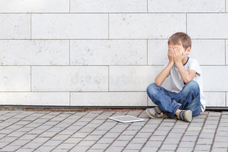 Weinig die jongen vermoeide droevig en met PC van de tabletcomputer beklemtoont Jong geitjezitting ter plaatse, holding zijn hoof stock fotografie