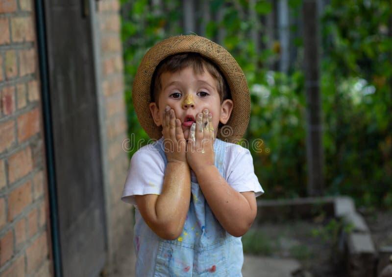 Weinig die jongenshanden in kleurrijke verven worden geschilderd Gelukkig jong geitje die pret hebben in openlucht stock foto's