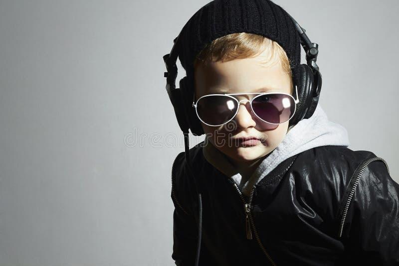 Weinig DJ grappige jongen in zonnebril en hoofdtelefoons Het luisteren van het kind muziek in hoofdtelefoons deejay royalty-vrije stock foto