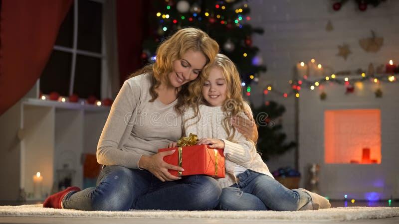 Weinig dochter aanwezige geven aan samen het houden van van moeder, die Kerstmis vieren royalty-vrije stock afbeelding