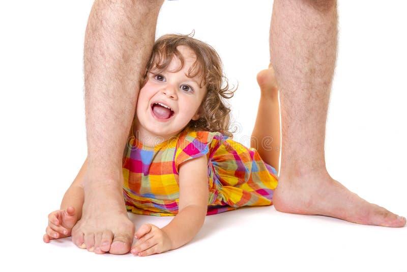 Weinig dochter bij de voeten van haar vader stock foto's