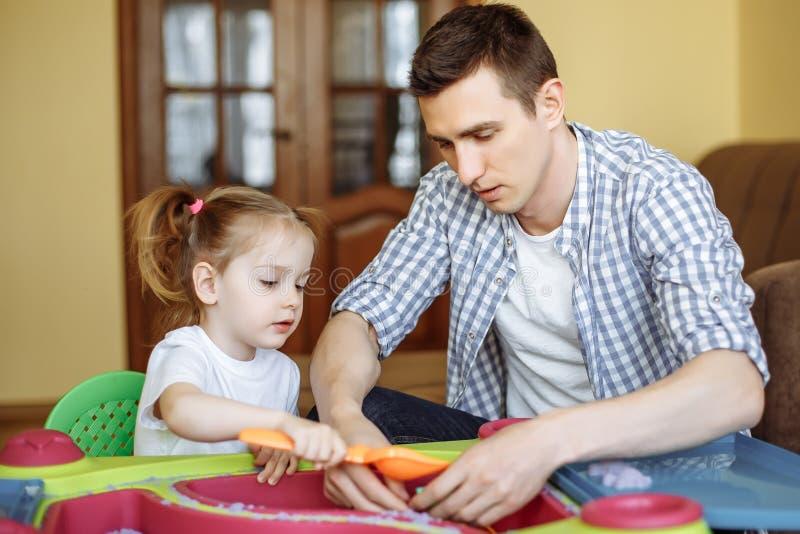 Weinig dochter en papa het spelen met kinetisch zand thuis Vormen voor zandspeelgoed Familiespelen stock fotografie