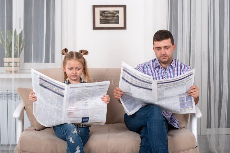 Weinig dochter en papazitting op de bank thuis en lezing de krant samen royalty-vrije stock afbeeldingen