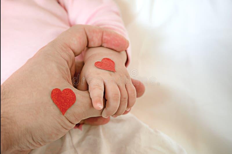 Weinig dochter houdt papa door de vinger harten voor de dag van p royalty-vrije stock afbeeldingen