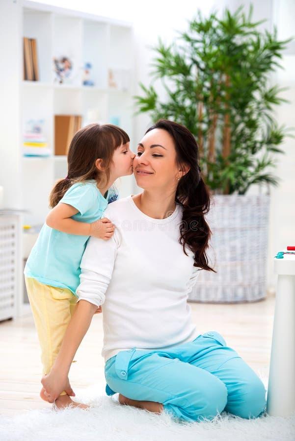 Weinig dochter koestert en kust mamma Gelukkige familie en liefde De dag van de moeder `s royalty-vrije stock foto's