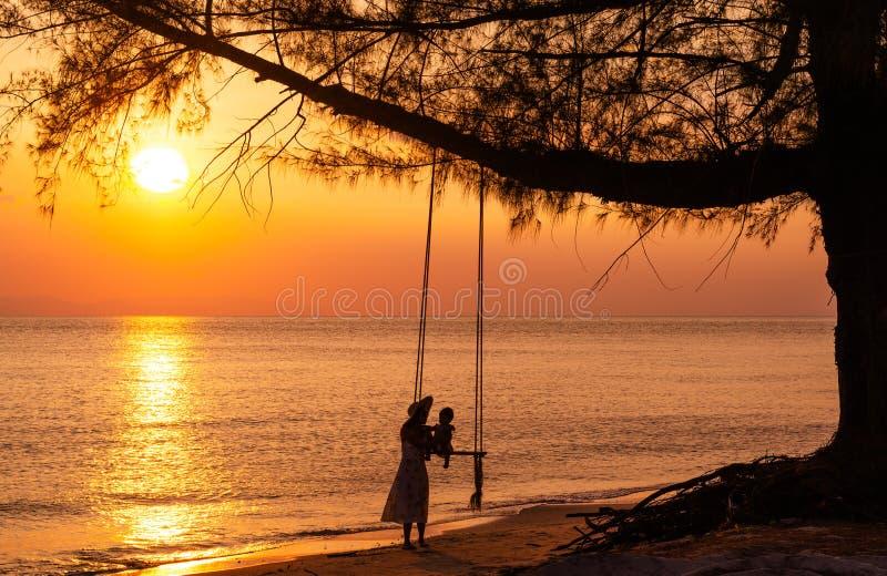 Weinig dochterzitting op een schommeling, de moeder geeft gelukkig haar weinig dochter door het overzees tijdens een mooie zonson royalty-vrije stock foto