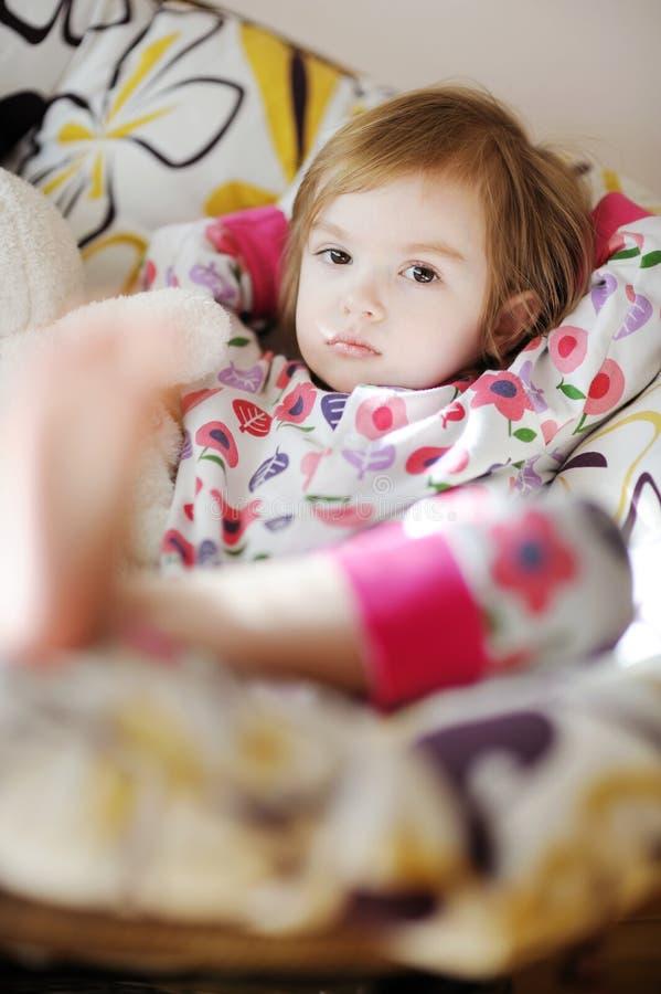 Weinig droevig meisje in pyjama's op zonnige ochtend stock fotografie