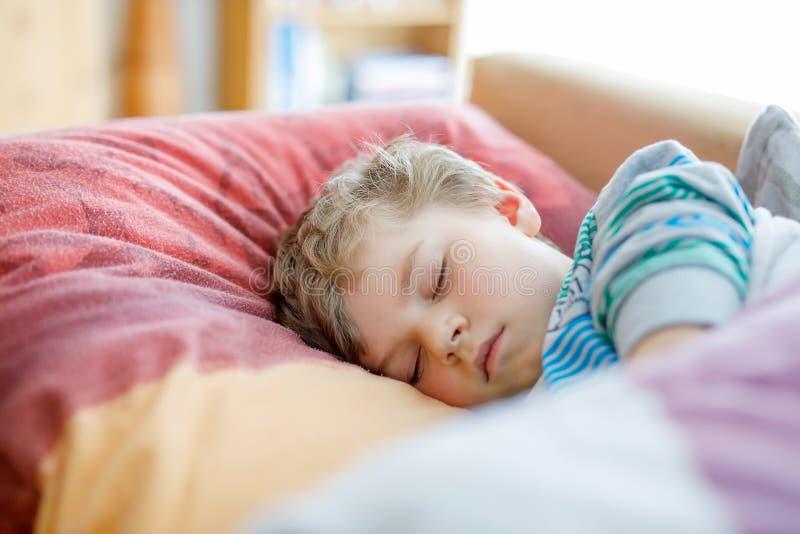 Weinig droevige peuterslaap van de jong geitjejongen Vermoeid schoolkind die na schoolklassen rusten stock foto's