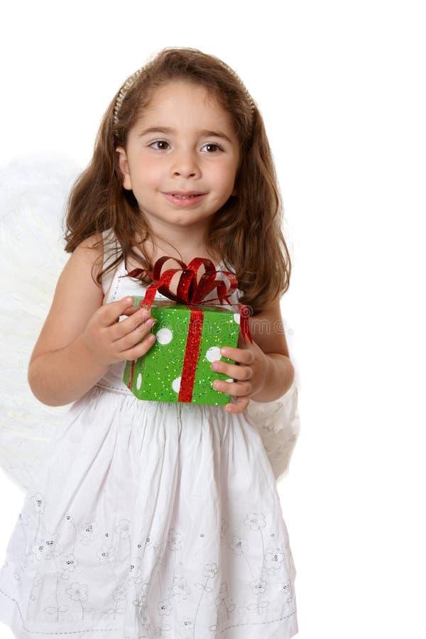 Weinig engelenmeisje dat een gift houdt stock foto