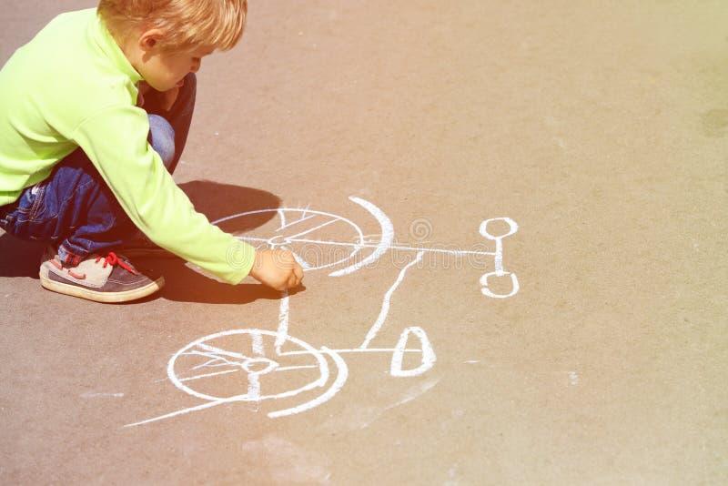 Weinig fiets van de jongenstekening op asfalt in openlucht royalty-vrije stock fotografie