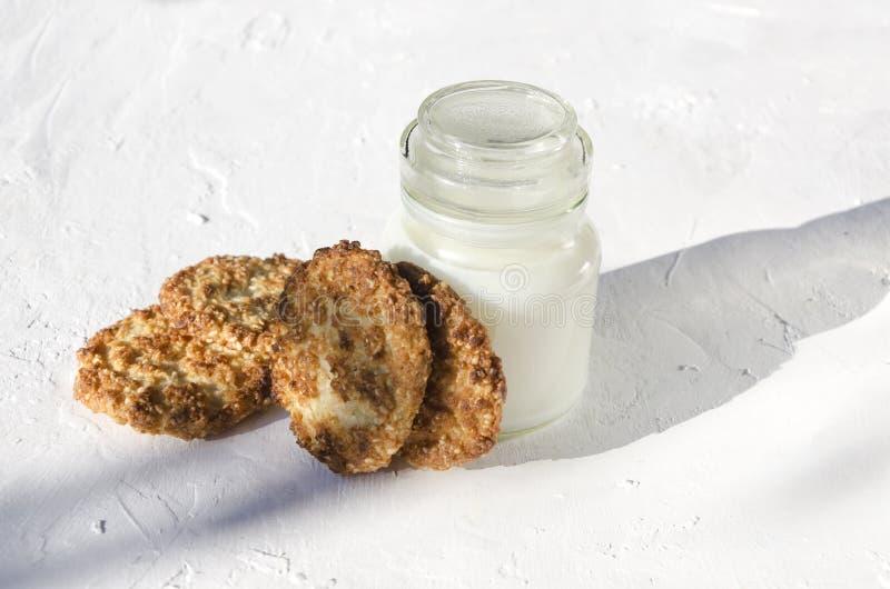 Weinig fles melk en lapje vlees van koekjes met sesam op de witte lijst, natuurlijk ochtendlicht stock foto