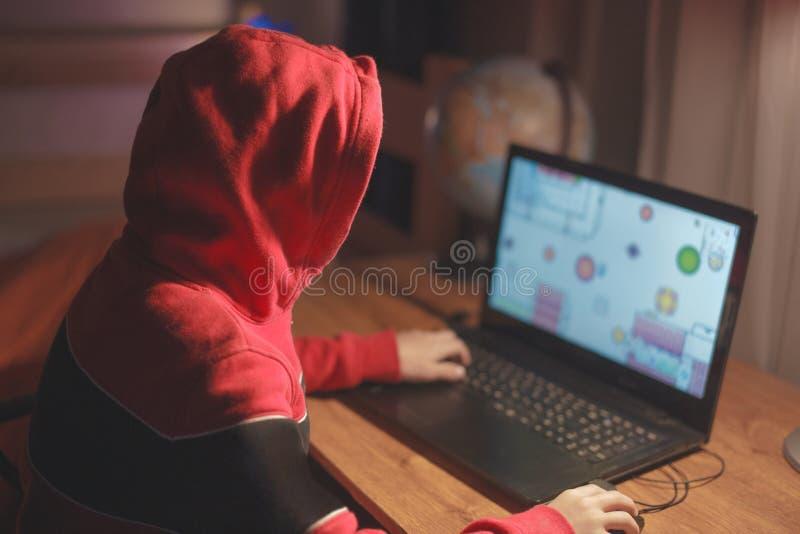 Weinig gamerjong geitje in spel van de kap het speelmassa multiplayer online op laptop royalty-vrije stock fotografie