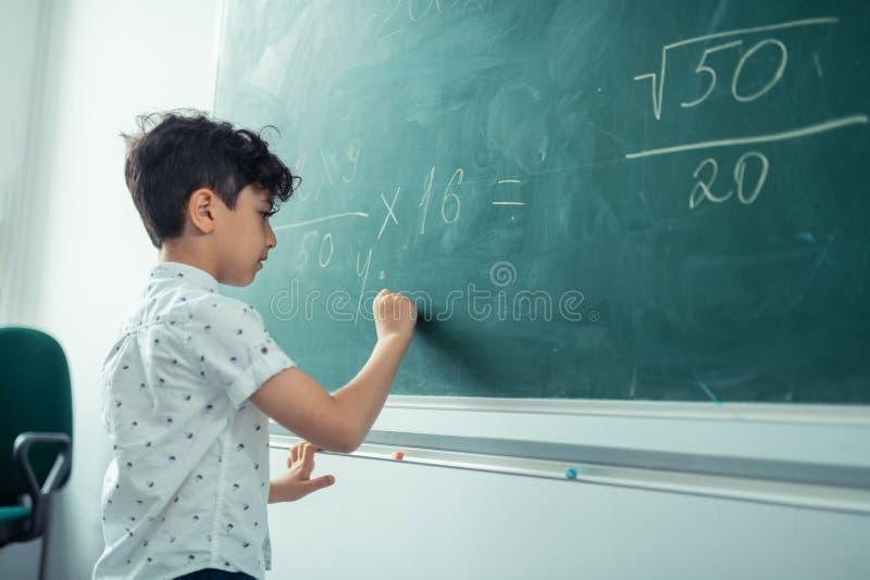 Weinig geconcentreerde schooljongen die op het bord schrijven stock foto's
