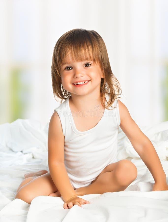 Weinig gelukkig glimlachend vrolijk meisje in een bed stock foto's
