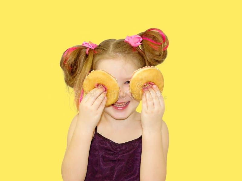 Weinig gelukkig leuk meisje eet doughnut op gele muur als achtergrond royalty-vrije stock foto's