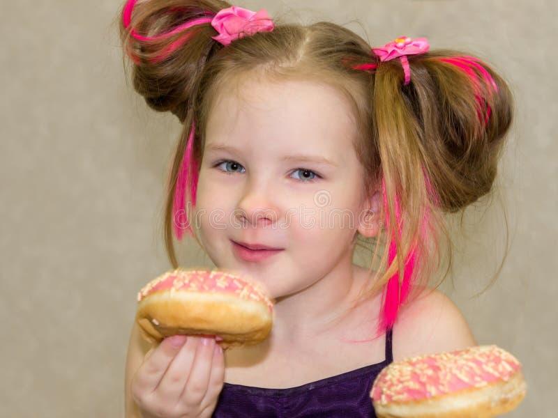 Weinig gelukkig leuk meisje eet doughnut op lichte muur als achtergrond royalty-vrije stock afbeeldingen