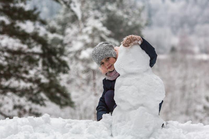 Weinig gelukkig meisje beeldhouwt sneeuwman in het de winterpark royalty-vrije stock foto's