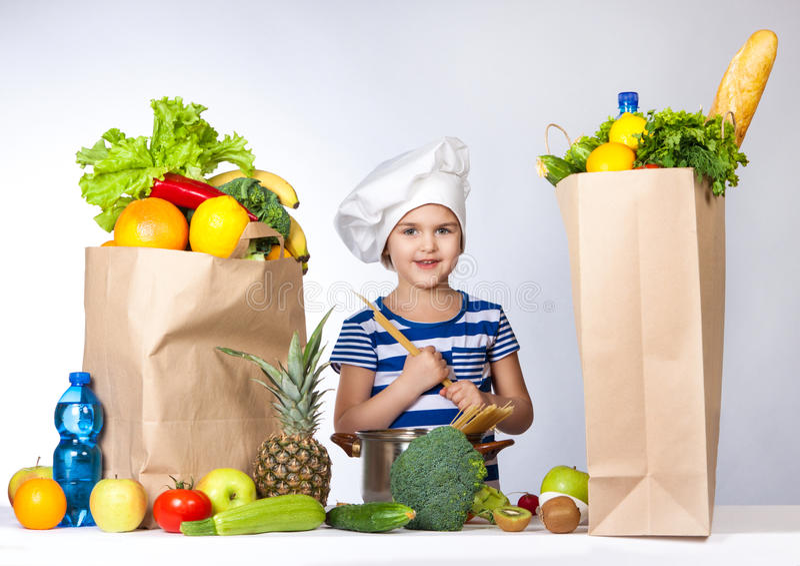 Weinig gelukkig meisje in chef-kokhoed met grote zakken van producten Het houdt in de handen van spaghetti stock afbeeldingen