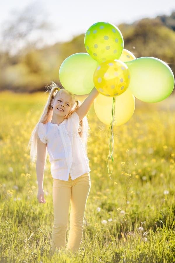 Weinig gelukkig meisje met groene en gele ballons stock fotografie