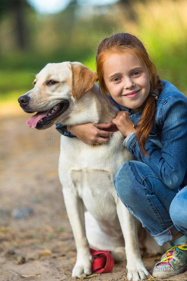 Weinig gelukkig meisje op een gang met de hond stock afbeeldingen