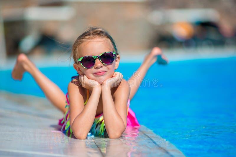 Weinig gelukkig meisje in openlucht zwembad geniet van haar vakantie stock fotografie