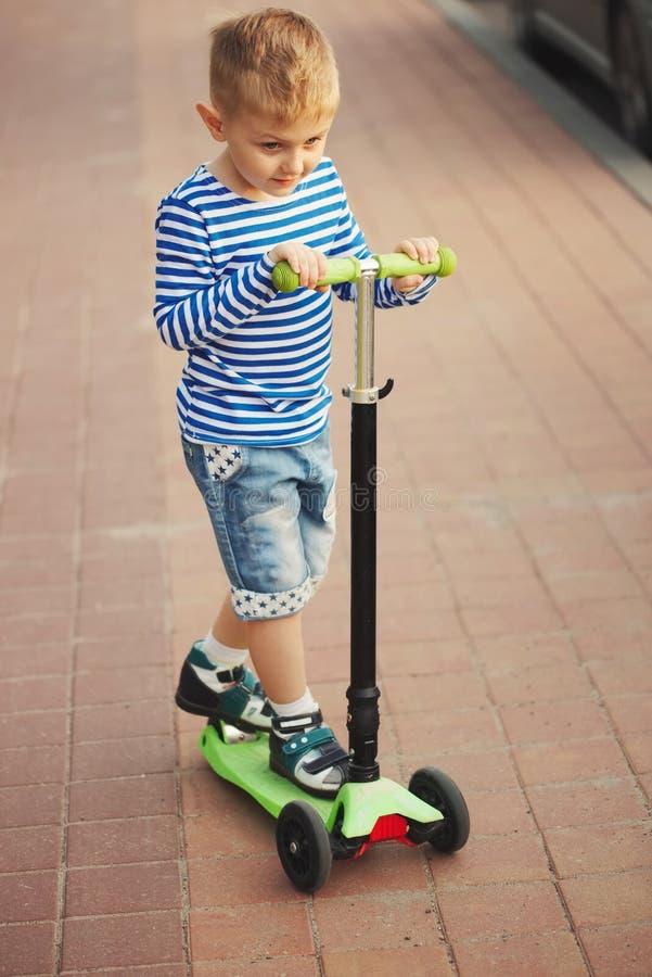 Weinig gelukkige jongen die op autoped berijden royalty-vrije stock fotografie