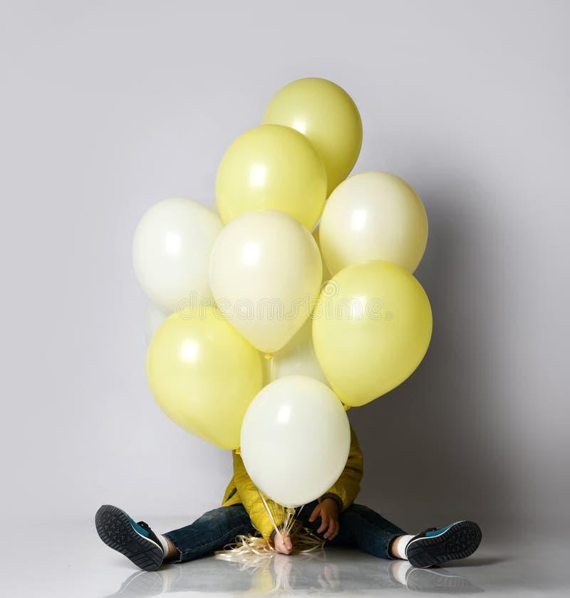 Weinig gelukkige jongen met kleurrijke ballons viert verjaardagspartij openlucht stock afbeelding