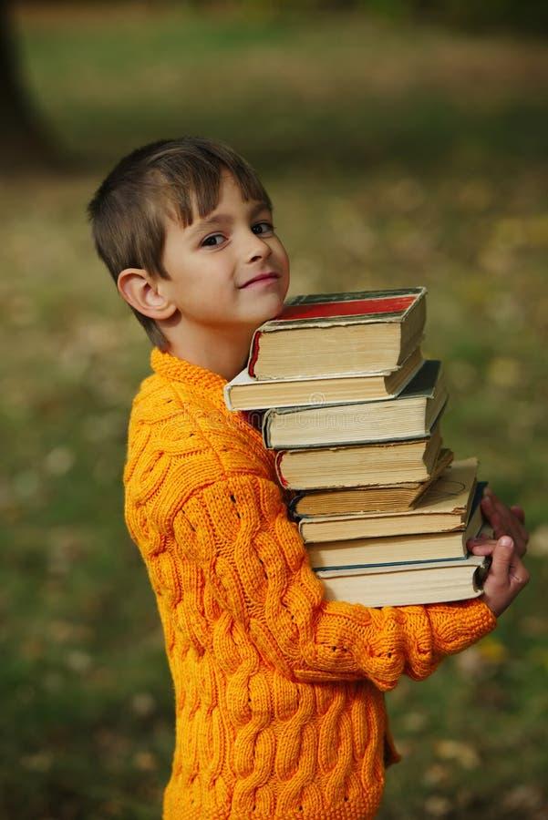 Weinig gelukkige jongens dragende stapel boeken royalty-vrije stock afbeeldingen