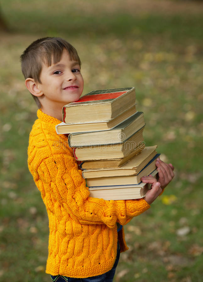 Weinig gelukkige jongens dragende stapel boeken stock afbeelding