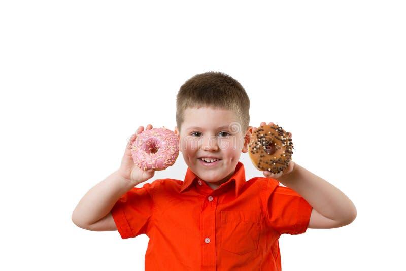 Weinig gelukkige leuke jongen eet doughnut op whte achtergrondmuur Het kind heeft pret met doughnut Smakelijk voedsel voor jonge  royalty-vrije stock afbeeldingen