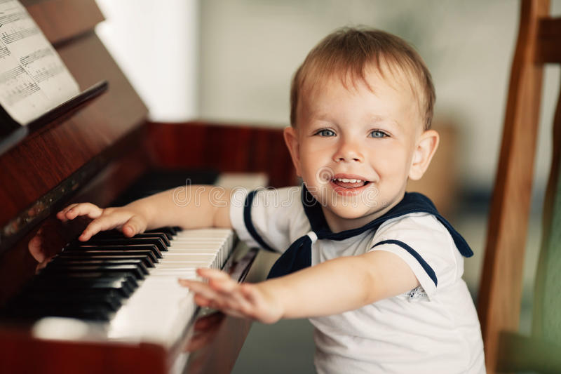 Weinig gelukkige piano van jongensspelen royalty-vrije stock foto's