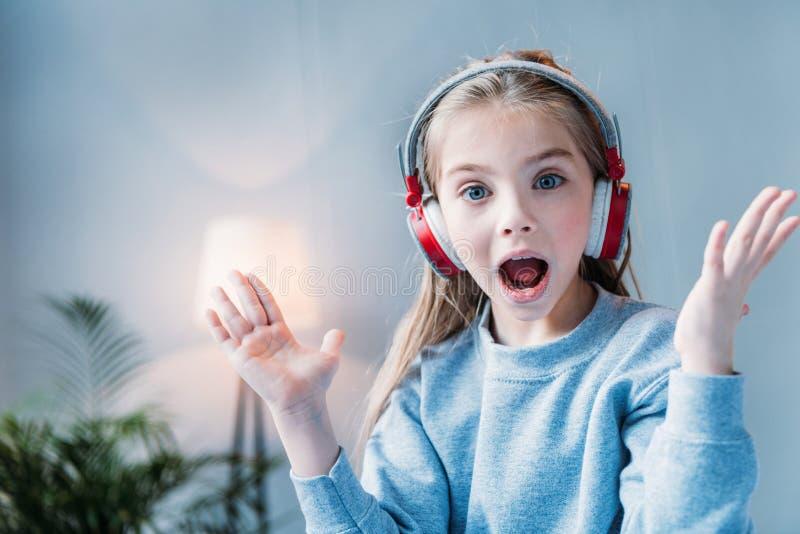 Weinig geschokte meisje het luisteren muziek in hoofdtelefoons stock foto's