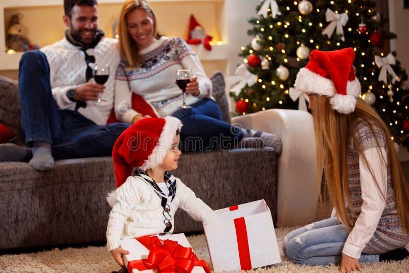 Weinig gift-doos van jongens open Kerstmis met familie stock foto's