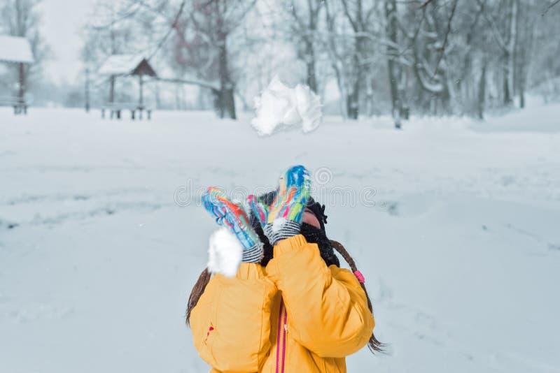 Weinig girlwith werpt de sneeuwwinter royalty-vrije stock afbeeldingen