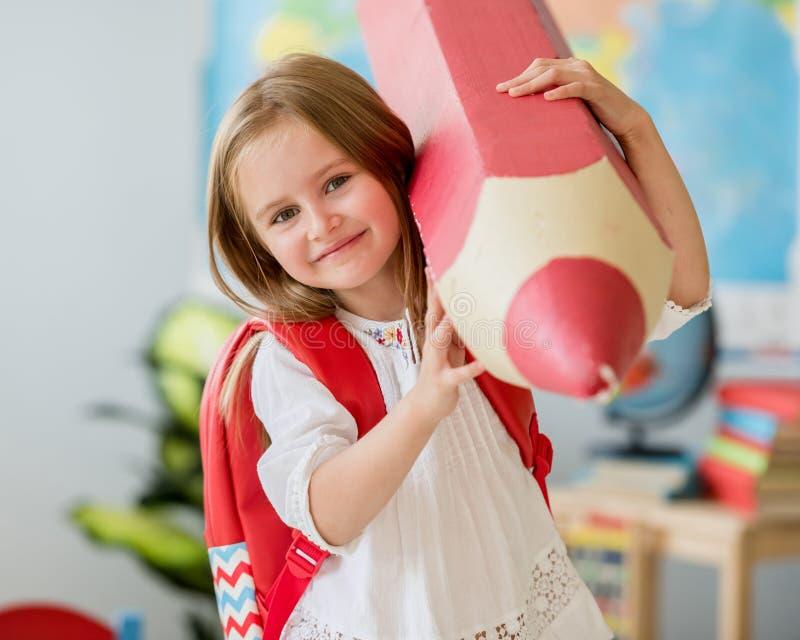 Weinig glimlachend blond meisje die reusachtig rood potlood in het schoolklaslokaal houden royalty-vrije stock foto