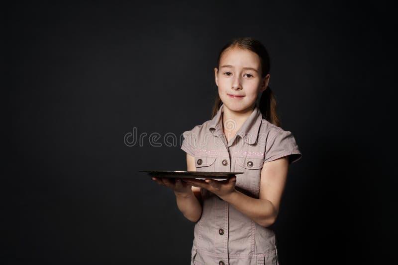 Weinig glimlachend Kaukasisch meisje houdt leeg voedseldienblad stock afbeelding