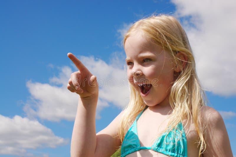 Weinig glimlachend meisje dat door vinger wordt gericht royalty-vrije stock foto