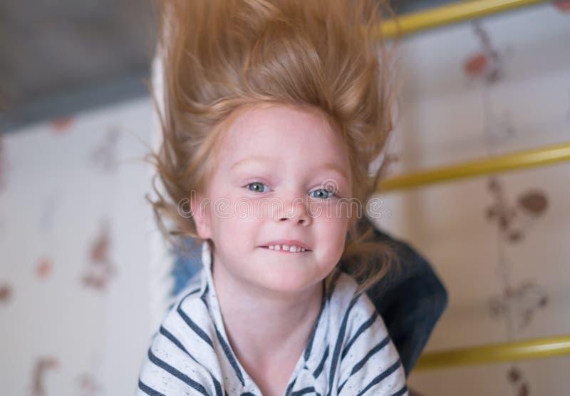 Weinig glimlachend meisje die dicht omhooggaand portret slingeren stock foto