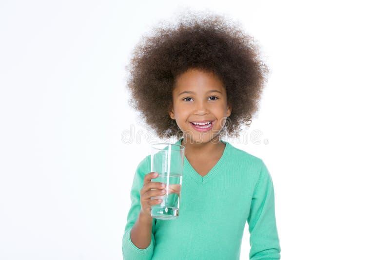 Weinig glimlachend meisje die een glas houden stock afbeelding