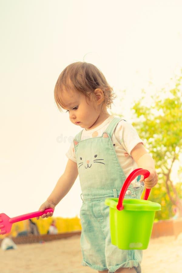 Weinig glimlachend meisje die met zand in zandbak in de zomer spelen stock foto