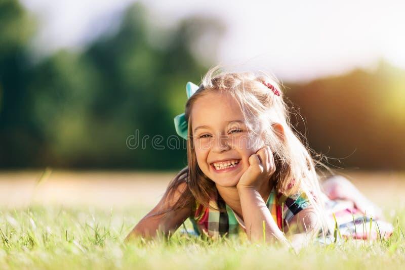 Weinig glimlachend meisje die op het grasgebied leggen in het park royalty-vrije stock foto