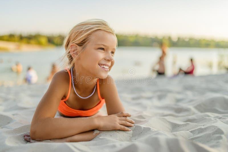 Weinig glimlachend meisje die op zand bij stadsstrand liggen stock foto's
