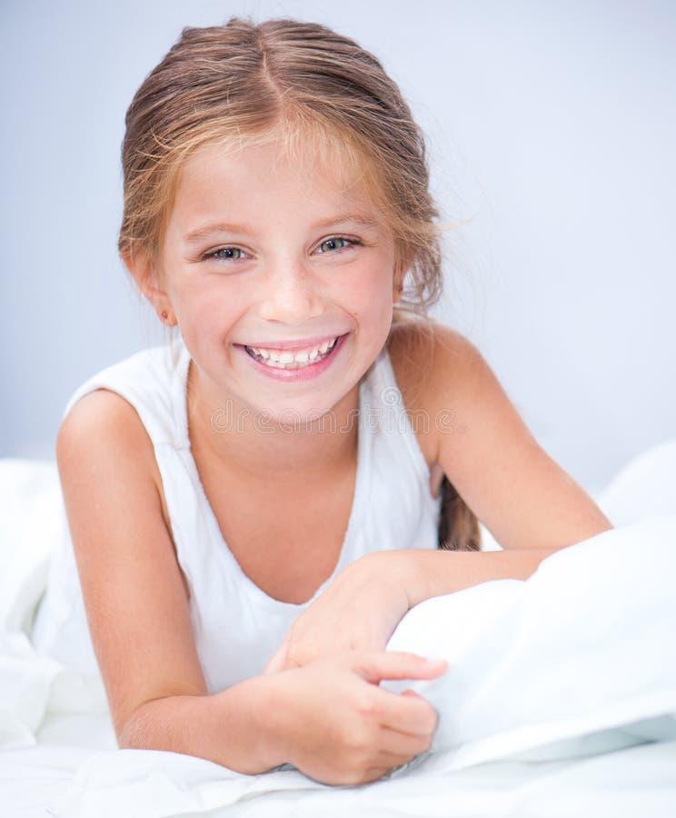 Weinig glimlachend meisje in een bed royalty-vrije stock afbeeldingen
