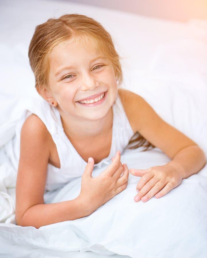 Weinig glimlachend meisje in een bed royalty-vrije stock afbeelding